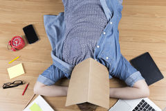 Woman lying on floor with mobile phone, notebook and laptop Stock Image