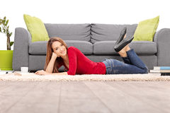 Woman lying on the floor next to a stack of books Royalty Free Stock Photo