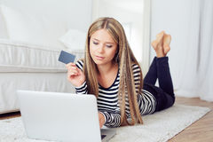Woman lying on the floor and shopping online Royalty Free Stock Photos
