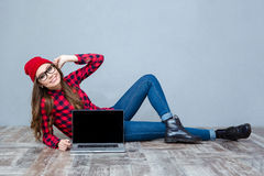 Woman lying on the floor and showing blank laptop screen Royalty Free Stock Photography