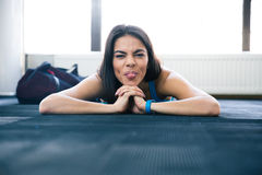 Woman lying on the floor and showing her tongue Royalty Free Stock Image