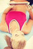 Woman lying on the floor with tablet pc Royalty Free Stock Photo