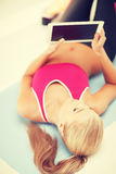 Woman lying on the floor with tablet pc Royalty Free Stock Images
