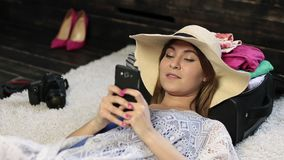 Woman lying on floor text messaging on cell phone stock video footage