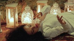 Woman is lying on the floor. Valentine`s Day. Girl in love. Young curly woman in white with beautiful red lips is lying on the carpet, against the background of stock video footage