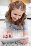 Woman lying on the floor working on her tablet Royalty Free Stock Photo