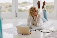 Woman working from home lying on floor stock photography