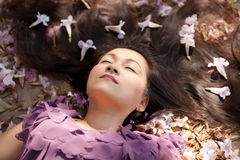 Woman lying in flowers Stock Image