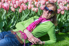 Woman lying in front of pink tulip field Royalty Free Stock Photo