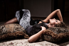Woman lying on a fur mat Royalty Free Stock Images
