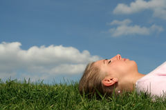 Woman lying on grass stock photography