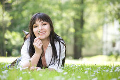 Woman lying on grass. Attractive brunette woman relaxing by lying on grass in park Stock Image