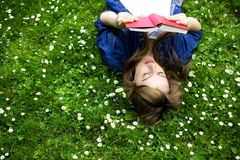 Woman lying on grass with book Royalty Free Stock Images