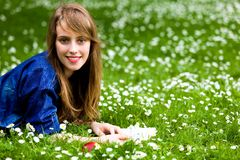 Woman lying on grass with book Royalty Free Stock Image