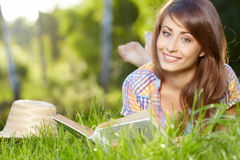Woman lying on the grass with a books Stock Photography