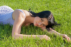 Woman lying on grass on bright sunny day. Royalty Free Stock Photography