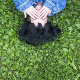 Woman lying on the grass covers his eyes with his hands, top view with space for text. Stock Photos