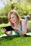 Woman lying on grass with digital tablet Stock Images