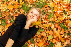 Woman lying on the grass with fallen orange leaves. A young beautiful woman in a black sweater and skirt is lying on the foliage on the grass, holding bright royalty free stock image