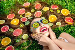 Woman lying on the grass with fruits around her hair a Royalty Free Stock Photography