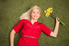 Woman lying on grass and holding a bunch of tulips Stock Photo
