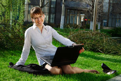 Woman lying on grass with laptop Stock Photo