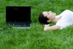 Woman lying on grass with laptop Stock Image