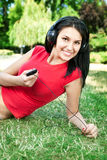 Woman lying on grass listening to music Stock Image