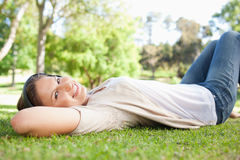 Woman lying on the grass while listening to music Royalty Free Stock Images