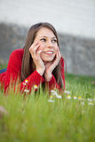 Woman lying in the grass with lots of flowers Stock Photography