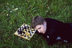 Woman lying in the grass near the chess board Stock Photo
