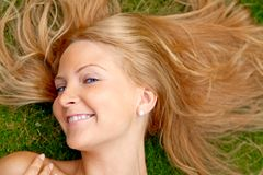Woman lying on grass outdoors Stock Image
