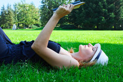 Woman lying in grass reading a book Royalty Free Stock Photos