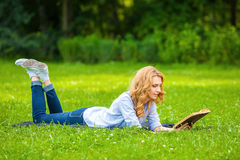 Woman lying in grass and reading a book Stock Images