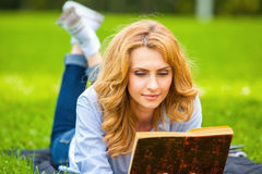 Woman lying in grass and reading a book Stock Photos