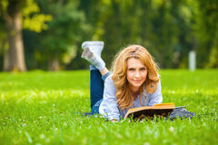 Woman lying in grass and reading a book Stock Photography