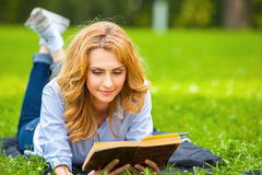 Woman lying in grass and reading a book Royalty Free Stock Image