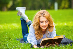 Woman lying in grass and reading a book Stock Image