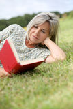 Woman lying in grass and reading book Royalty Free Stock Images