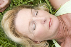 Woman lying in grass sleeping Stock Images