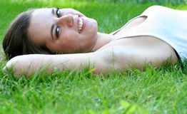 Woman lying on grass, smiling Stock Image