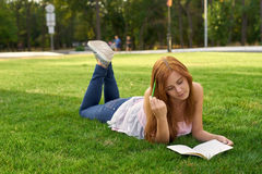 Woman lying on the grass and teaches lessons.  Royalty Free Stock Photography