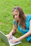 Woman lying on the grass while using her laptop Royalty Free Stock Photography