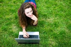 Woman lying on the grass using laptop Royalty Free Stock Photo