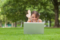 Woman lying on grass and using laptop at the park Stock Photos