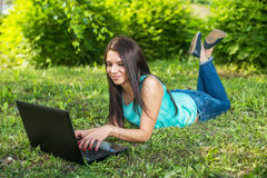 Woman lying on the grass, using laptop and typing Stock Images