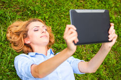 Woman lying in grass and using a tablet Stock Photo
