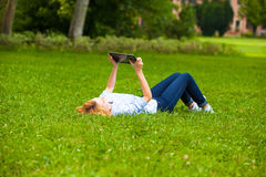 Woman lying in grass and using a tablet Royalty Free Stock Images