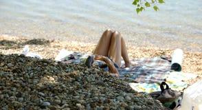 Woman Lying on Gravel Beach Stock Photo