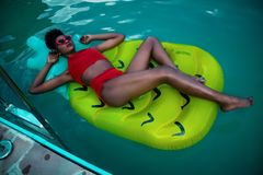 Woman Lying on Green Float Wearing Red Bikini stock photos